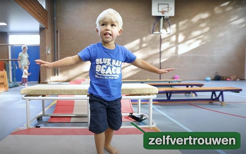 jongetje is in een gymzaal aan het gymmen